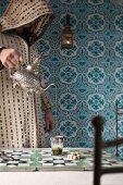 Mann serviert Pfefferminztee in einem Cafe in Marrakesch (Marokko)
