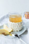 Quince tea with fresh quince pieces and a handmade crochet sleeve