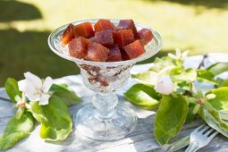 Quittenbrotwürfel in einer alten Glasschale auf Tisch im Freien, daneben Äste mit Quittenblüten