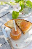 An outdoor breakfast with quince marmalade in a jar and on white bread, with quince flowers and branches