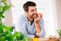 A man leaning on a kitchen counter eating an apple