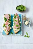 Open baguette sandwiches topped with spinach, basil, ham and Camembert
