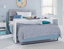 Boxspringbett mit Bettbrücke im Schlafzimmer in blauen Tönen