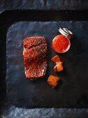 Smoked salmon and salmon caviar on a black tray