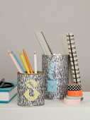 Metalldosen dekoriert mit farbigen Dreiecken im Tangram-Stil mit Schreibutensilien