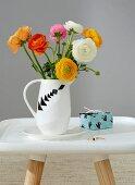 Ranunkelstrauss in weißem Krug mit verschiedenen Tangram-Motiv und kleines Geschenk