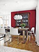 Essplatz mit weissen, lederbezogenen Schalenstühlen um Eichentisch, gegenüber Buffet an bordeauxroter Wand