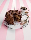 A chocolate buttercream cake with a slice cut out