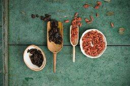 Getrocknete Cranberries und Gojibeeren in Holzschaufeln und Schälchen auf rustikalem Holzuntergrund