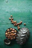 Haselnüsse mit und ohne Schale in einem Backförmchen auf rustikalem Holzuntergrund