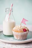 A raspberry muffin with white chocolate next to a small bottle of milk with a straw