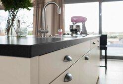 Kücheninsel mit weißem Unterschrank, Muschelgriffe und eingebautem Spülbecken