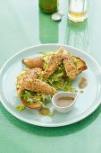 Chicken goujons in a peanut coaching on slices of grilled baguette