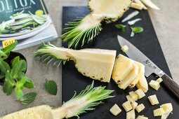 Freshly cut pineapple on a black chopping board