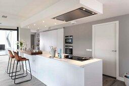 Moderne Küche in Weiß mit freistehender Theke, oberhalb abgehängtes Deckenfeld mit Beleuchtung und Dunstabzug