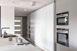 Ausschnitt einer Küchentheke, gegenüber moderner Einbauküchenschrank in Weiß in offener Küche