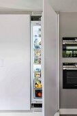 Raumhoher Einbauschrank mit offener Kühlschranktür