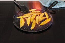 Pfanne mit flambierten Mangostücken auf Induktionsherd