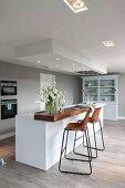 Moderne Küche in Weiß mit Einbaustrahlern in abgehängter Decke, Barhocker mit Holzschale auf Metallgestell vor freistehender Theke