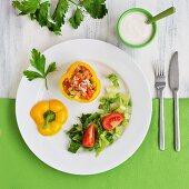 Gelbe Paprikaschote, gefüllt mit Salat aus Reis, Paprika und Tomaten