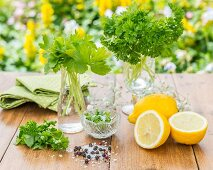 Flat-leaf and curly-leaf parsley in glasses with lemons and spices in the foreground