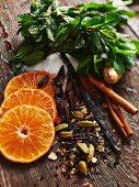 Various ingredients for hot drinks (oranges, spices, ginger, sugar, mint)