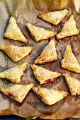 Puff pastry rhubarb turnovers on a piece of baking paper