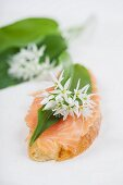 A slice of baguette topped with smoked salmon, a wild garlic leaf and edible wild garlic flowers