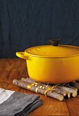Yellow cast-iron casserole with lid on wooden mat