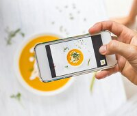 A woman using a smartphone to take a picture of carrot and pumpkin soup