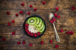 A smoothie bowl with amaranth, chia seeds, raspberries and kiwi (seen from above)