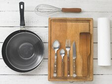 Kitchen utensils: a pan, a whisk, cutlery and a spatula