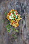 A potato fritter waffle with crème fraîche, herbs and tomatoes