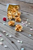 Waffle bites in a paper bag with mini marshmallows in front of it