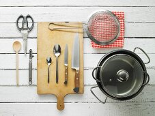 Kitchen utensils: pots, a sieve, knives, spoons, scissors and a peeler