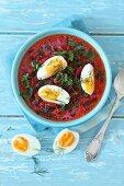 Rote-Bete-Suppe mit zarten Rote-Bete-Blättern, Sahne und hartgekochtem Ei