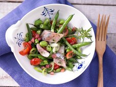 Soused herring & bean salad with cherry tomatoes and bacon