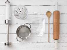 Kitchen utensils: a hand blender, a pot, a measuring jug, a rolling pin and a wooden spoon