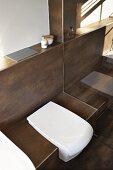 weiße Toilette in geflieste braune Sitzfläche integriert, Vormauerung mit Drückerplatte