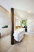 Geschwungener, weißer Waschbeckenunterbau in elegantem Designerbad mit Duschbereich und Fotokunst