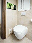 weiße Toilette unter Einbauschrank und Fotokunst an Fliesenwand