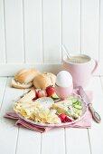 Käsefrühstück mit Ei, Radieschen, Erdbeeren, Gurken, Brötchen und Kaffee