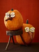 Three Halloween pumpkins with funny fruit and vegetable faces