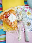 A slice of apricot tart with marzipan on a crystal plate