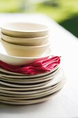 Stack of plates, bowls and napkins on garden table