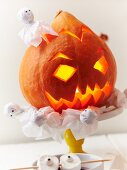 An illuminated Halloween pumpkin and ghosts as party decorations