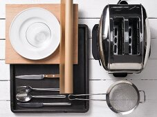 Assorted kitchen utensils: cutlery, crockery, a baking tray and a toaster