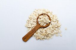 A pile of barley flakes with a wooden spoon on a white surface