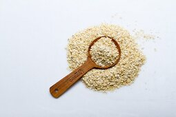 A pile of millet flakes with a wooden spoon on a white surface