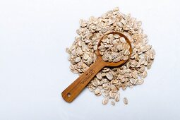 A pile of rye flakes with a wooden spoon on a white surface